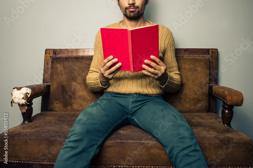 Young man reading on old sofa