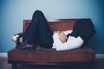Businessman sleeping on old sofa