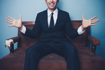 Excited young businessman on sofa