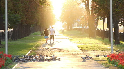 Man and woman in park walking away to heaven, sun