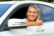 Happy woman giving thumb up inside her new car