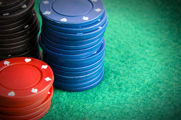 Closeup of poker chips in stacks on green felt card table