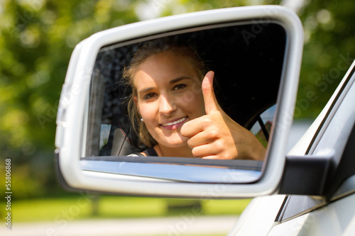 Female car driver with thumb up