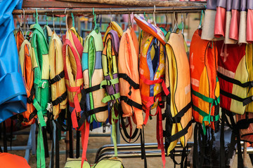 Old colorful life jackets for rent.