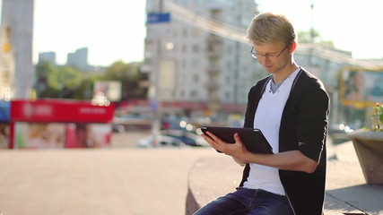 Young male with tablet pc pad smiles reads device