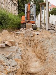 Strassenbau - Ein Minibagger hebt einen kleinen Graben aus