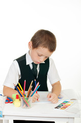 little boy at his desk with  pencils and books