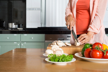 Midsection Of Woman Cutting Vegetables At Kitchen Counter