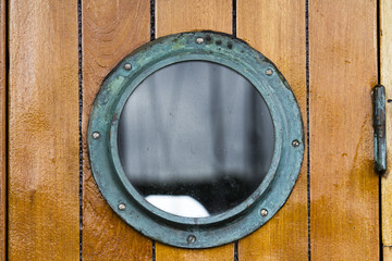 Boat porthole close up wood planks