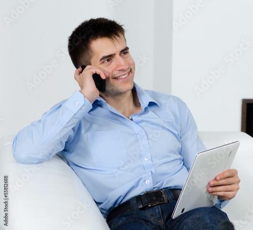 freundlicher mann mit tablet am telefon