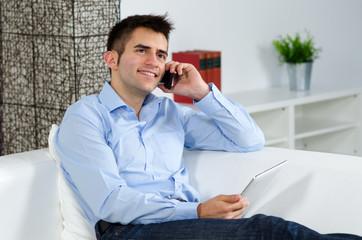 freundlicher mann am telefon mit tablet
