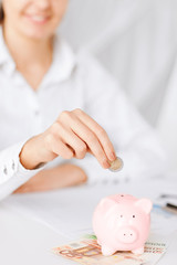 woman hand putting coin into small piggy bank