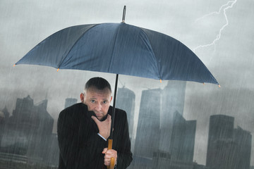 Depressed businessman under the rain