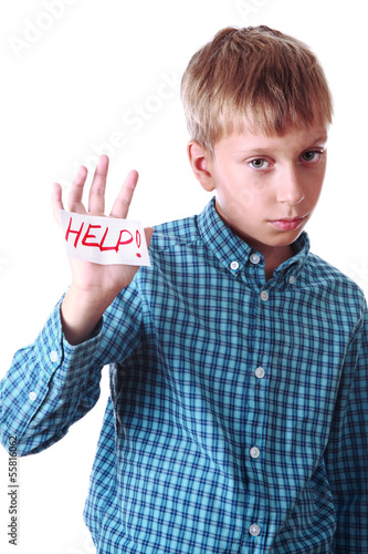 "Beautiful boy in a shirt shows a message ""Help!"""