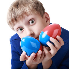 Cute blond boy holds two colorful plastic eggs