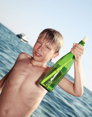 Cute blond boy in a swimming suit holds a bottle with a message