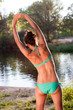 Girl in bikini doing stretching exercises beside a river
