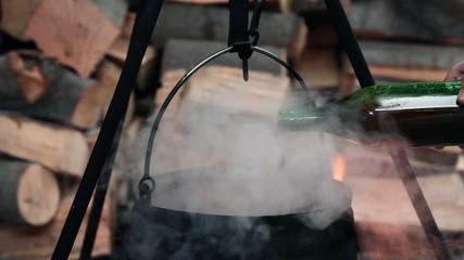 Tomato juice pouring into boiling cauldron