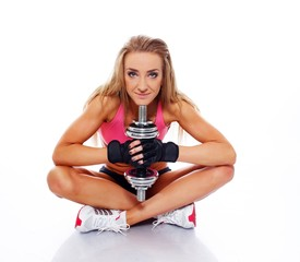 Sporty woman with dumbbell sitting on floor