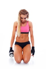 Sporty woman with dumbbell standing on her knees