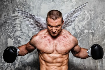 Young boxer with angel wings behind his back