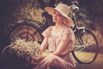 Beautiful retro woman with basket of flowers