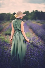 Woman in long green dress and hat in a lavender field