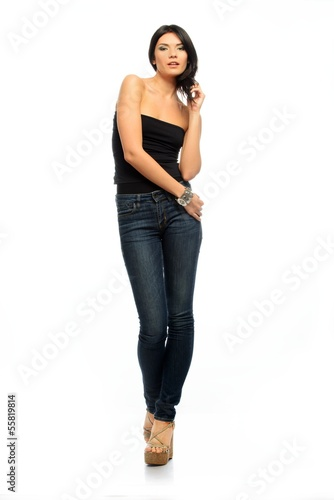 Young beautiful brunette woman in black top and jeans