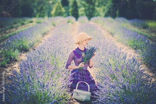 Woman in purple dress and hat with basket in lavender field
