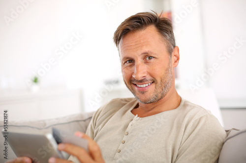 Handsome smiling man at home buying on internet