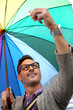 Man in town with rainbow umbrella
