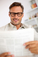 Friendly guy with eyeglasses reading newspaper