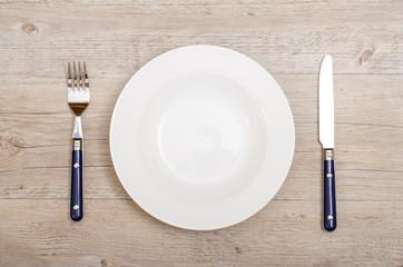 Blaue Messer und Gabel und weisser Teller