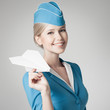 Charming Stewardess Holding Paper Plane In Hand. Gray Background