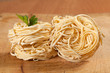 Nests of dry pasta on wooden table.