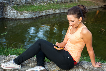 Young woman using smartphone at park