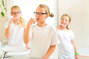 Mädchen beim Zähne putzen im Bad