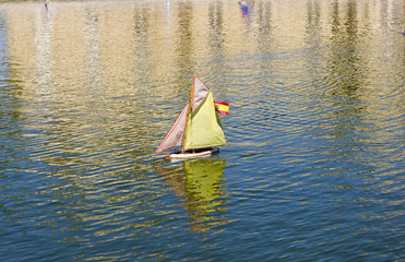 Traditional small wooden sailing boat in the pond of park Jardin