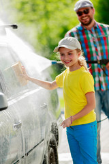 Carwash - young girl helping father to wash car.