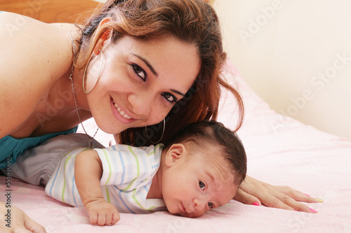 Hispanic mom lying down on bed and holding her infant son