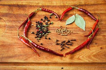 Dried red chili peppers and spices in heart shape on rustic, dar