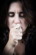 Portrait of a beautiful latin woman kissing a crucifix