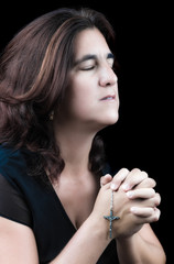 Hispanic woman praying with her eyes closed