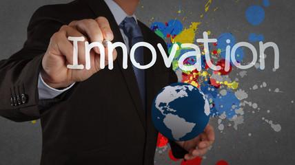 businessman hand writing innovation on splash color background