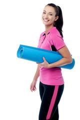 Gym instructor holding blue mat