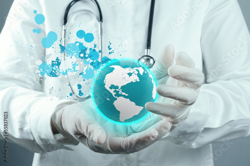 Doctor Holding  World Globe and splash colors In Her Hands