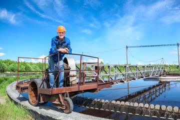 Senior worker standing on waste water treatment unit on plant