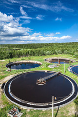 Huge circular settlers of sewage treatment plant under blue sky