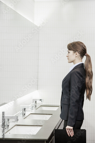 Young businesswoman with long hair looking into the mirror and preparing herself in the bathroom