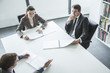 Three business people sitting around a table and having a business meeting, high angle view